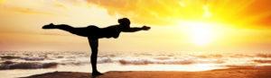 Woman yoga pose on sunset beach