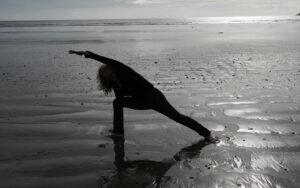 Christine Stewart doing Parsvakonasana on beach
